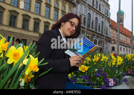 Woman sitting on a row of flower planters reading a travel guide, Munich, Bavaria, Germany, Europe - Stock Photo