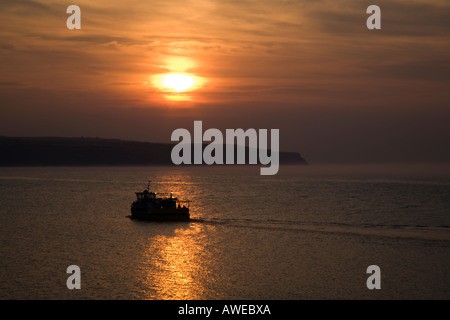The Summer Sunset Cruise Sails across the Bay at Whitby North Yorkshire England - Stock Photo