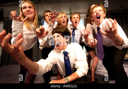 Teenagers in school uniforms in a drama class - Stock Photo