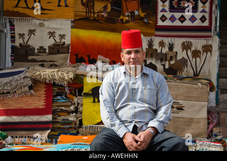 Egyptian man selling carpets in souk in Old Sharm Sinai Egypt - Stock Photo