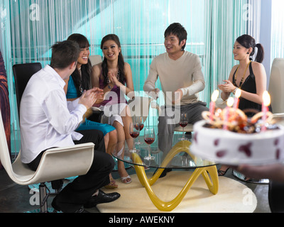 young men and women celebrating, someone bringing the birthday cake - Stock Photo
