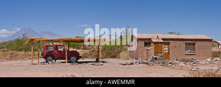 Four-wheel drive vehicle parked under sun shade in front of a small clay house, Licancabur Volcano in background, - Stock Photo