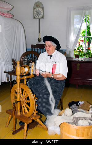 A demonstration of spinning wool with a spinning wheel at The Mennoniate Heritage Village in Steinbach Manitoba - Stock Photo