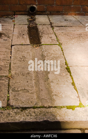 Rainwater channels for garden run off chiselled into Victorian Edwardian paving slabs Cardiff UK - Stock Photo