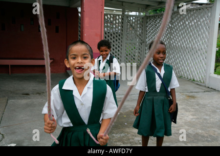 Girls dressed in school uniforms playing with a skipping rope at an Ursuline convent and orphanage in Georgetown, - Stock Photo
