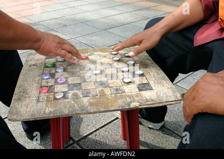 A couple of men playing draughts with the bottle top, Bangkok, Thailand - Stock Photo