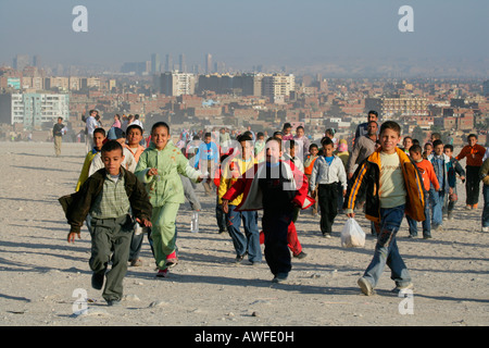 Class trip to the pyramids, Cairo blanketed in smog in the background, Egypt, North Africa, Africa - Stock Photo