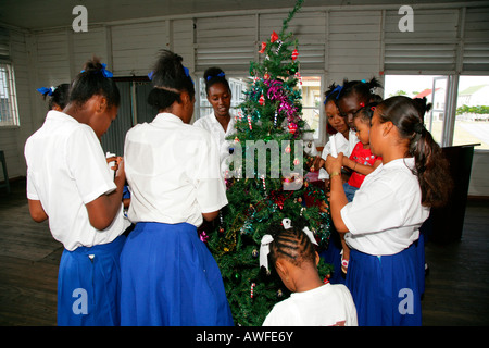 Girls wearing school uniforms decorating a Christmas tree at a training centre for young women in New Amsterdam, - Stock Photo