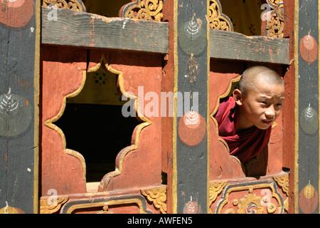 A novice monk playing in the courtyard of the Paro dzong, Bhutan - Stock Photo