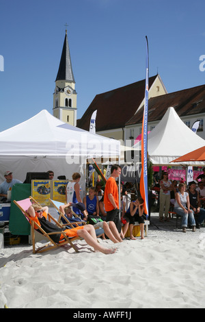 Kids sitting on deck chairs, spectators at a beach volleyball tournament on the main square of Muehldorf am Inn, - Stock Photo