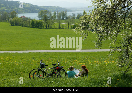 Female cyclists examining a map beside Tachinger See (Lake Taching), St. Coloman, Upper Bavaria, Bavaria, Germany, - Stock Photo