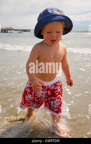 Little boy on the beach running through the water, Caorle, Veneto, Italy - Stock Photo