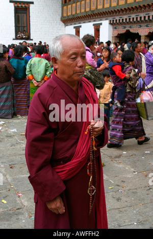 A monk in the Thimphu dzong during the Tsechu (festival), Bhutan - Stock Photo