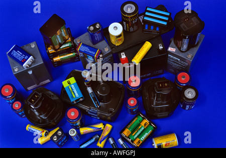 Old rechargeable batteries against a blue backdrop - Stock Photo