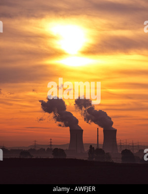 Nuclear power plant cooling towers in a colourful evening sky - Stock Photo