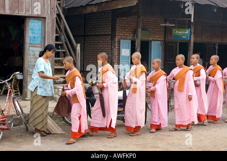 Stock photograph of a young Buddhist nuns making their daily rounds begging for food at Nyaungshwe in Myanmar - Stock Photo