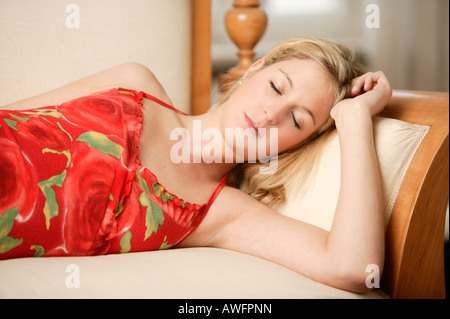 Young blonde woman sleeping on couch - Stock Photo