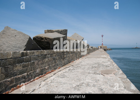 Perspective shot of pier in Montevideo, with small lighthouse in its end - Stock Photo