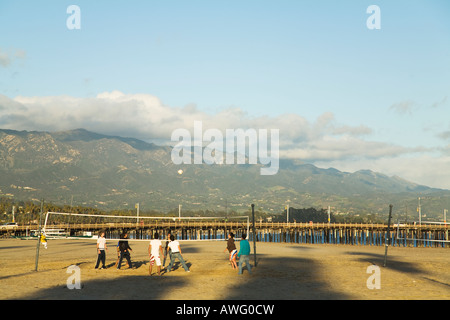 CALIFORNIA Santa Barbara High school students playing beach volleyball on West Beach Stearns Wharf and mountains - Stock Photo