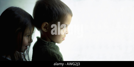 Big brother and little sister look out from doorway - Stock Photo
