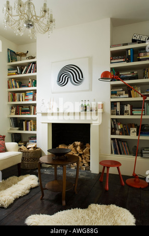 Living room with sheepskin and mantelpiece in London townhouse - Stock Photo
