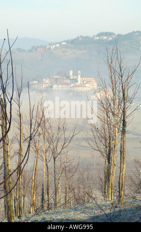 An old farm and through the mist emerges the town of Monterchi on the border between Tuscany and Umbria Italy - Stock Photo