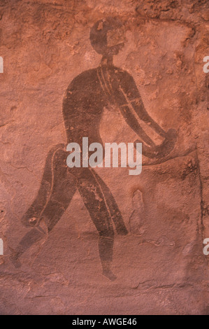 Algerian Sahara Tassili N'Ajjer Sefar neolithic rock painting of figure using grindstone Algeria - Stock Photo