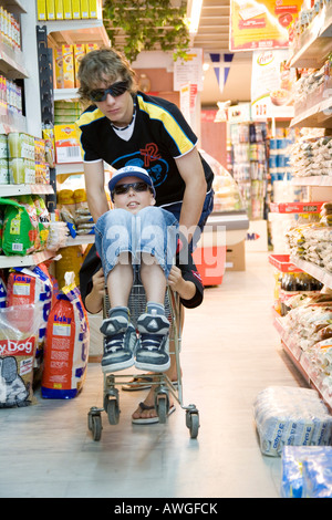 kids playing while shopping in the supermarket - Stock Photo
