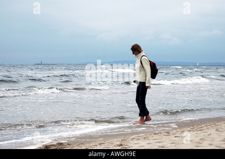 Woman walking on the beach, Baltic seashore in Swinoujscie, Poland - Stock Photo