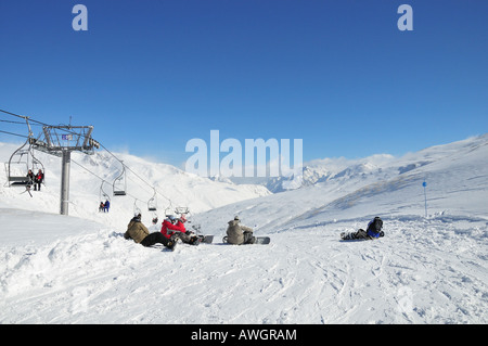 Snowboarders resting on a ski slope in the Pyrenees, Pas de la Casa skiing resort, Andorra (Spain) - Stock Photo