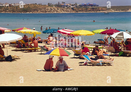 Turkey, holidaymakers sunbathing on sandy beach and seated under colourful umbrellas - Stock Photo