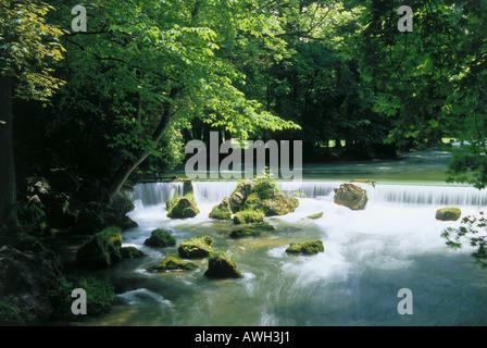 Germany, Bavaria, Munich, Englischer Garten, rapids on stream shrouded by trees - Stock Photo