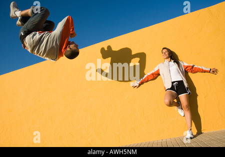Woman leaning on yellor wall, man somersaulting on front of her - Stock Photo