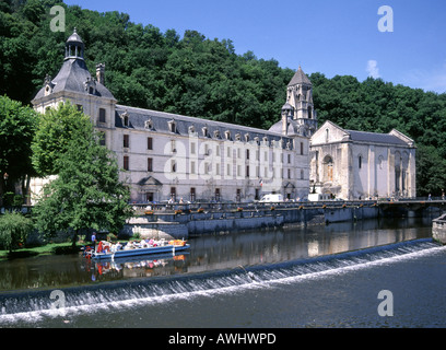 Benedictine Abbey of Brantome and its bell tower beside river Dronne with tour boat and weir - Stock Photo