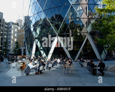 businessmen office workers having lunch lunchtime at the base of the Swiss Reinsurance building a k a the gherkin - Stock Photo