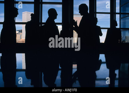 Business people in a board room silhouetted against a skyline background - Stock Photo