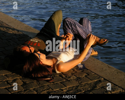 Young couple enjoying the sun on the banks of the Seine in Paris France - Stock Photo
