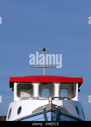 Pilot house on a small fishing cutter against a bright blue sky - Stock Photo
