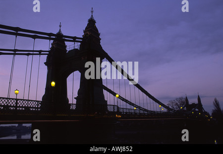 A view of Hammersmith suspension bridge in West London at dawn on the river Thames, England, UK - Stock Photo
