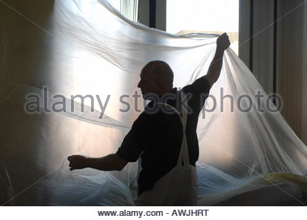 decorators office furniture. painters and decorators protecting office furniture prior to spraying paint stock photo