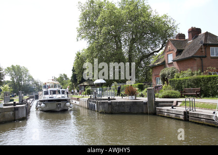 Cabin cruiser motor yacht pleasure boats passing through Mapledurham Lock near Purley on Thames on River Thames - Stock Photo