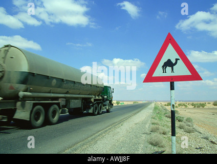 Jordan, tanker on road next to camel crossing sign - Stock Photo