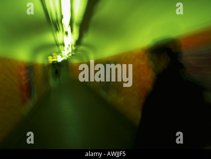 Blurred figures walking through tunnel - Stock Photo