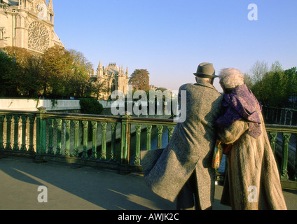 France, Paris, elderly couple walking arm in arm on bridge next to Notre Dame Cathedral - Stock Photo
