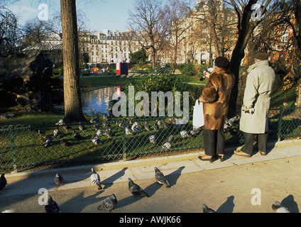 France, Paris, couple and pigeons in park - Stock Photo