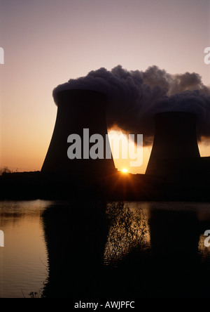 Nuclear reactors reflected in water at sunrise - Stock Photo