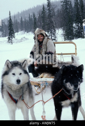 Sweden, man sitting on sled pulled by sled dogs - Stock Photo
