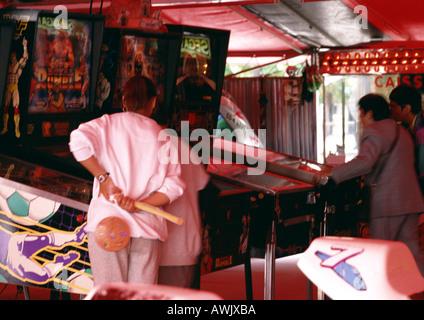 People playing pinball at arcade. - Stock Photo