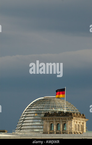 German flag and new cupola by Sir Norman Foster on the old Reichstag building in Berlin's government district. - Stock Photo