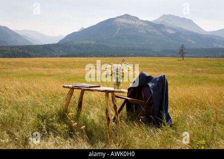Table in a field of golden grass to register a wedding in Rocky mountains Alberta Canada - Stock Photo
